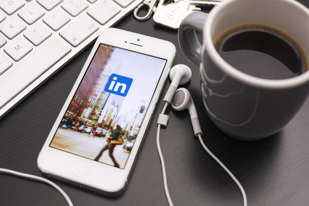 A phone displaying the LinkedIn logo next to headphones, a mug of coffee and a laptop, representing Further's online qual research work with LinkedIn.