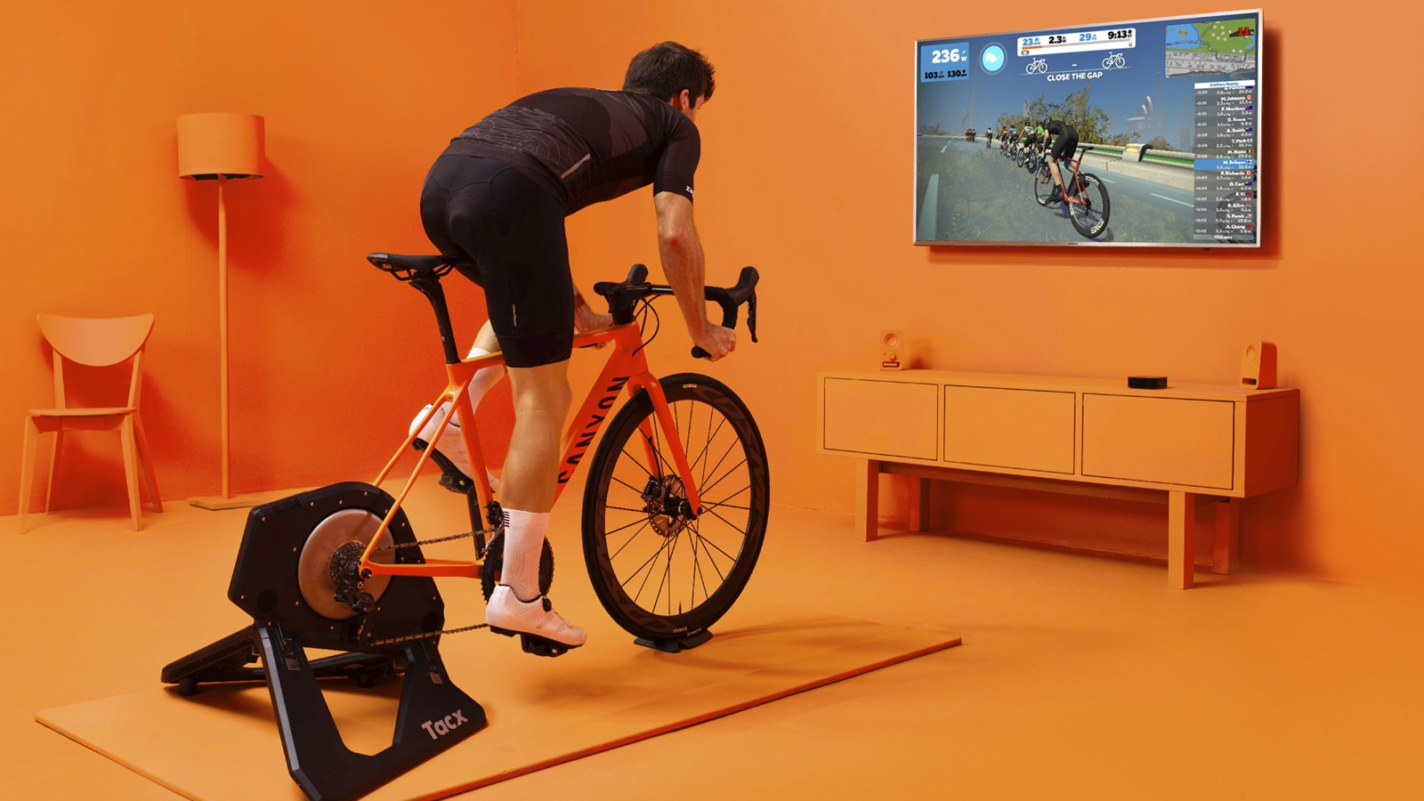 A man on a bike watching a TV in an orange room, representing Further's online qual research work with Zwift.